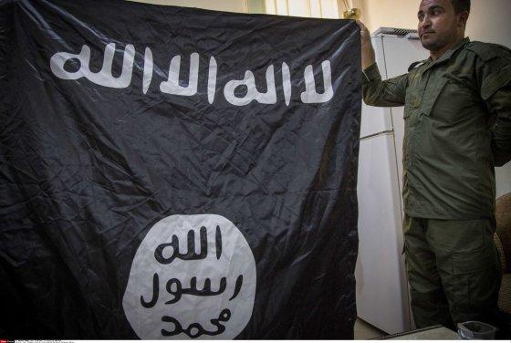 """""""Scanpix""""/""""SIPA"""" nuotr./Kurdų karys laiko po mūšių su džiahadistais paimtą """"Islamo valstybės"""" vėliavą"""