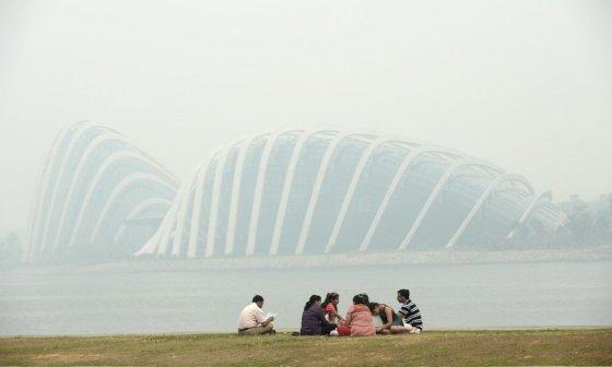 """AFP/""""Scanpix"""" nuotr./Nepaisydami oro taršos singapūre ilsisi grupelė žmonių"""