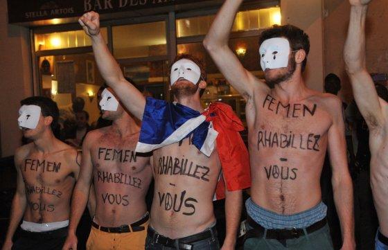 """AFP/""""Scanpix"""" nuotr./Tai ne gėjų eitynės, o vienalyčių santuokų priešininkų akcija. Judėjimo Hommen nariai protestuoja prie feminisčių organizacijos Femen būstinės Paryžiuje"""