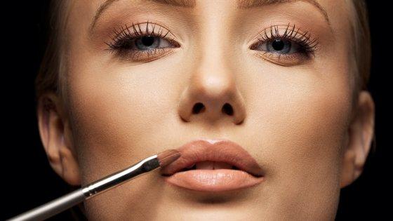 Shutterstock nuotr./Moteris dažo lūpas