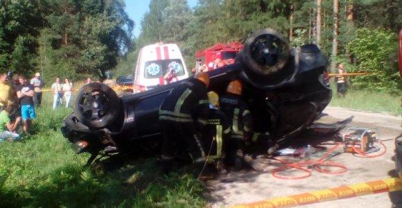 Su BMW X5 medį nulaužusius ir apsivertusius jaunuolius vadavo ugniagesiai