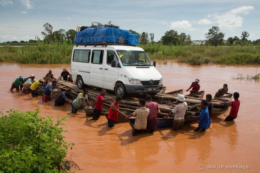 Akvilės Norkutės nuotr./Madagaskare po lietaus patvinus upei nemaža dalis kelio atsidūrė po vandeniu, tad autobusiukas gelbėjamas savadarbiu keltu